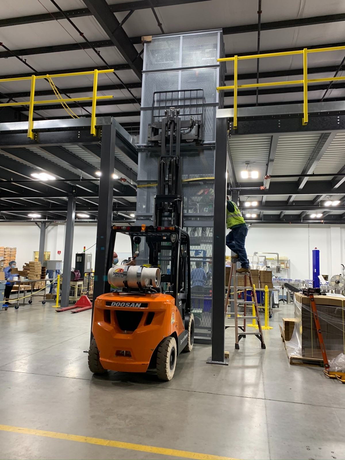 mezzanine conveyor construction using electric forklift